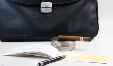 чековая книжка и сигара на фоне портфеля