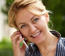 женщина говорит по мобильному и улыбается